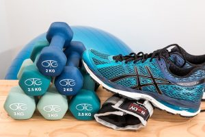 small blue and green dumbbells stacked next to a running shoe