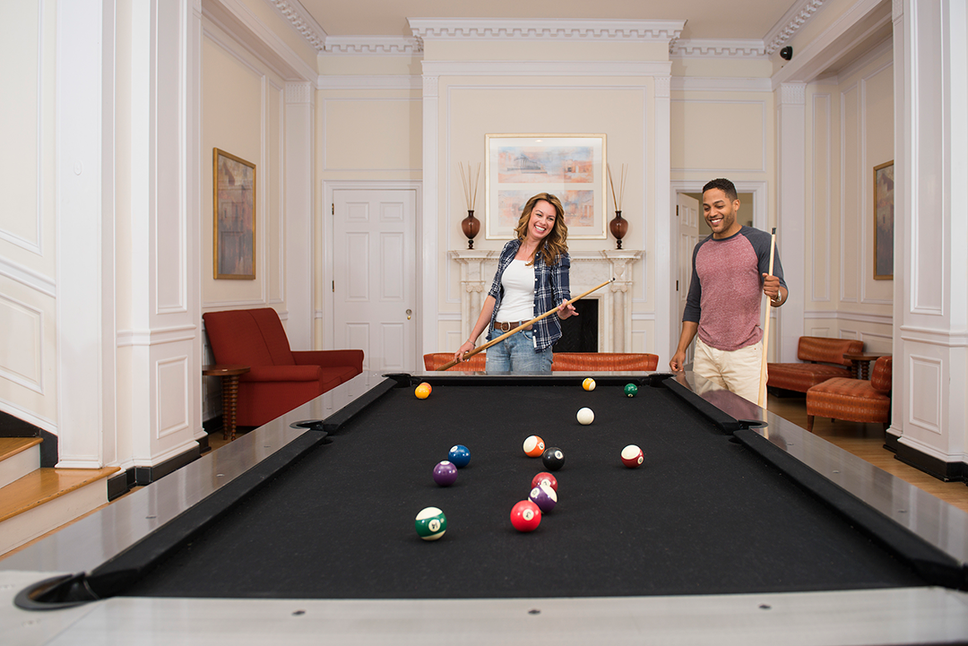 couple playing pool at lounge in apartments in wilmington de